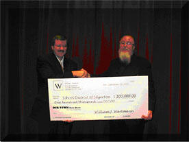 William Wartmann presents a check to Dr. Norman L. Fjelstad, Superintendent of the School District of Edgerton.